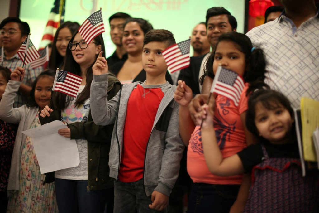 Children say the pledge of allegiance during a ceremony to present citizenship certificates to young people who earned citizenship through their parents, in Los Angeles, California