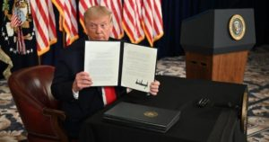 Trump holding up an Executive Order.