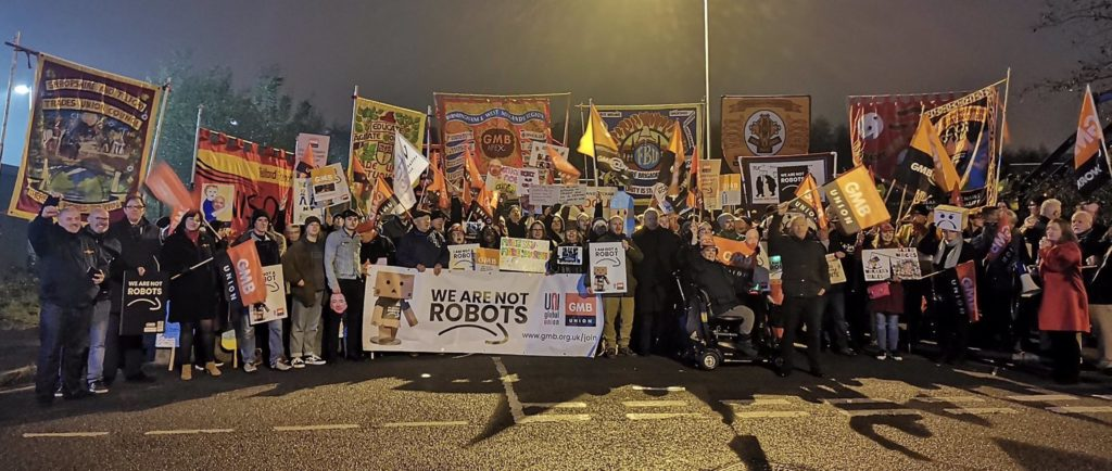 Living Wages: Featured image: Unionized Amazon workers in the U.K. and across Europe protest pay and working conditions. (GMBUnion@Amazon)